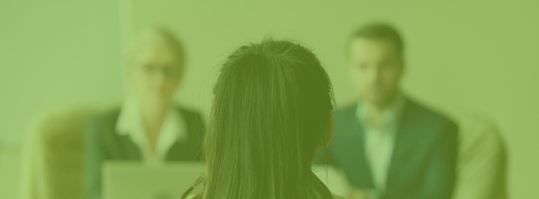 Une jeune femme de dos pendant un entretien d'embauche