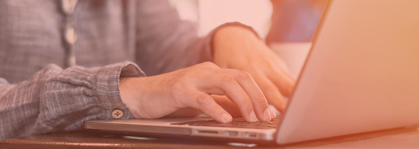 Une personne tape sur clavier d'ordinateur portable