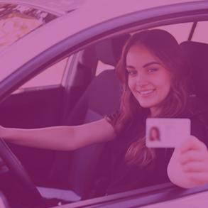 Jeune femme au volant d'une voiture et montrant son permis de conduire